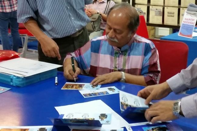 Prof Dato Raja Zahabuddin Raja Yaacob autographing Coronation Sultan Johor FDCs
